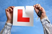 Tearing L plate against a sky holding a car key after passing driving test