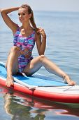 SUP Stand up paddle board woman paddle boarding on lake standing happy on paddleboard on blue water. poster