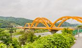 Landscape Of Yellow Arched Railroad Bridge Spanning A River In The Countryside On A Cloudy Overcast  poster