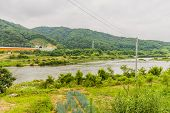 Landscape Of River Valley With Yellow Bridge And Mountains In Background Under A Cloudy Overcast Sky poster