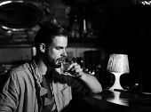 Guy With Serious Face Drinks Shot Or White Rum At Bar Counter. Man With Beard Drinks Alcohol In Bar  poster