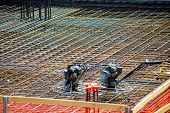 Closeup Of Steel Rebars. Geometric Alignment Of Rebars On Construction Site Reinforced Steel Rods Fo poster
