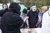 LONDON, UK - OCTOBER 31: Protesters wearing masks are answering questions of public and giving away