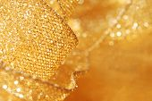 Holiday background image of gold sparkly mesh ribbon on metallic fabric with copy space.  Macro with extremely shallow dof.