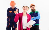 Female Foreman Concept. Woman In Hard Hat With Smiling Face Has Idea, In Front Of Male Builders In U poster
