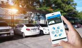 Hand Holding Smart Phone And Application Dashboard With Blur Car Parking Background. poster