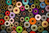 Bright Composition Of Wooden And Plastic Sewing Spools With Colorful Vibrant Threads From Above poster