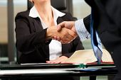 Mature female lawyer or notary with client in her office - handshake