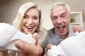 Senior couple, man and woman, laughing & having fun playing video console games together.