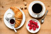 Croissant, Cup Of Black Coffee, Fresh Raspberries, Cream And Jam On Wooden Table. Continental Breakf poster