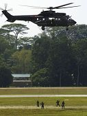 stock photo of guardsmen  - Guardsmen rappeling from a transport helicopter Singapore