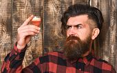 Man Holds Alcohol Cocktail On Wooden Background. Suspicious Drink Concept. Barman With Beard And Ser poster