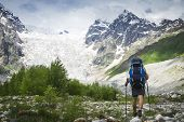 Hiker Trekking In The Mountains. Climber With Tourist Backpack Goes To Rocky Mountain Covered With S poster