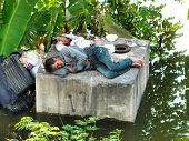 PHATHUMTRANI, THAILAND- OCTOBER 21: Flood victim becomes homeless, sleeps above the concrete, during the worst flooding in decades on October 21, 2011 Rongsit Road, Phathumtrani, Thailand.