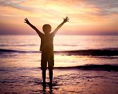 Silhouette of a boy with hands raised in the sunset over the sea concept for religion, worship, pray poster
