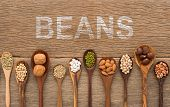 Beans And Lentils In Wooden Spoon With White Painted On Wood Background. Groundnut, Walnuts, Macadam poster
