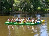 Seven canoes with young people grouped in the middle of the river