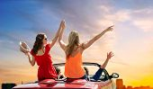 summer holidays, road trip and travel concept - happy friends driving in convertible car at country  poster