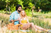 Affectionate Couple Hugging And Sitting On Grass At Picnic poster