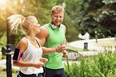 Young couple jogging in park poster