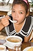 girl tastes the boiled rice