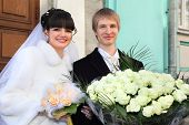 Smiling bride and groom with bouquets of roses stand near registry office