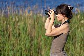woman watching wildlife with binoculars in swamp area