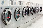 foto of oversize load  - A row of stainless steel industrial washing machines
