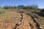 picture of superstition mountains  - A dirt trail outlined by rocks leads deep into the Superstition Mountain range in the Arizona desert - JPG