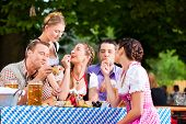 In Beer garden - friends Tracht, Dirndl and on a table with beer and snacks in Bavaria, Germany