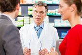 Pharmacist is consulting customers - a man and a woman - in his pharmacy