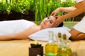 Beautiful Asian woman having a wellness Head massage in a tropical setting and feeling visibly good about it