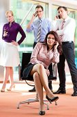 Business people - female boss and employees in office, all making a call with their mobiles