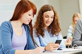 Two young women looking at their smartphone in university class