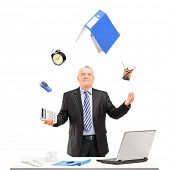 stock photo of juggling  - Mature businessman juggling in his office - JPG