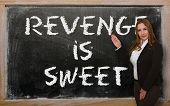 stock photo of revenge  - Successful beautiful and confident woman showing revenge is sweet on blackboard - JPG