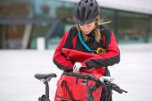 Young female cyclist in protective gear looking through courier delivery bag