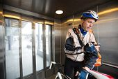 Young male cyclist with courier delivery bag using mobile phone in an elevator