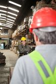 Portrait of young foreman with arms crossed standing at warehouse