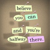The saying Belive You Can and You're Halfway There on pieces of paper pinned to a bulletin board to
