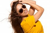 Positive young woman in yellow shirt with sunglasses over white background