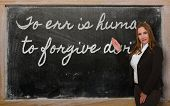 Teacher Showing To Err Is Human, To Forgive Divine On Blackboard