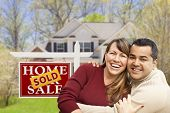 stock photo of real  - Happy Mixed Race Couple in Front of Sold Home For Sale Real Estate Sign and House - JPG