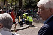LONDON, UK - APRIL 21: Male runner on London Marathon receiving help from Police officers after suffering from convulsion on April 21, 2013 in London, UK.