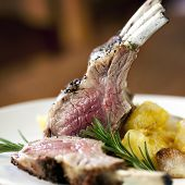 stock photo of lamb chops  - Rack of lamb with rosemary and roasted potatoes - JPG