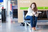 Mulher pensativa com dispositivos eletrônicos perto lugar para carregar seu telefone