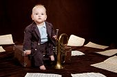 Caucasian Baby Boy Plays With Trumpet Between Sheets With Musical Notes Against Brown Background