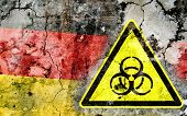 picture of biohazard symbol  - Old cracked wall with biohazard warning sign and painted flag flag of Germany - JPG