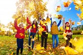 pic of 5s  - Group of five kids boys and girls throwing autumn maple leaves in the park on sunny day - JPG