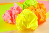 Colorful crumpled paper balls on table close up